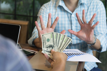 Business man hand saying no sign to money dollar note to bribery. Stop corruption concept.