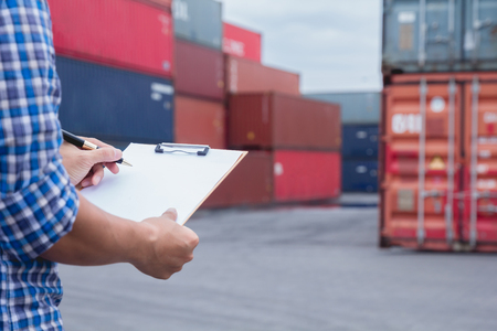 Man taking note checking cargo shipping at container yard area. Worker man signing papers about import - export logistic business. Stock Photo