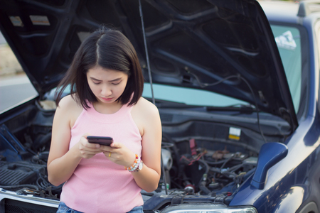 Young woman standing by broken car on the road and using smartphone calling assistance.Asian girl using mobile phone at breaking down car on street contacting car technician or need help.