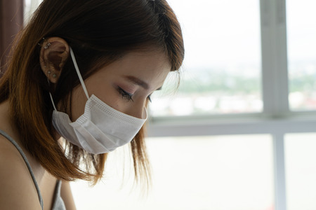 Woman wearing protective face mask because of air pollution in the city