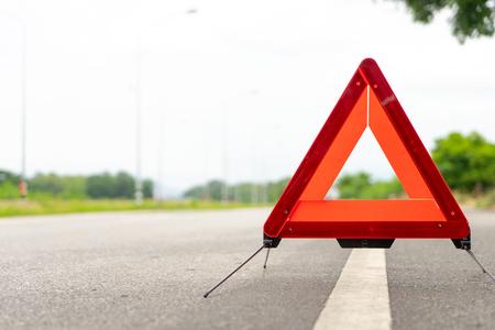 pechdriehoek staat langs de weg. De auto brak teken op wegconcept. Stockfoto
