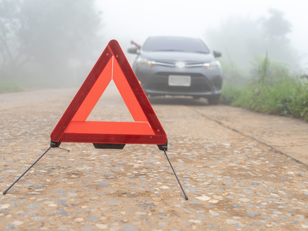 A car breakdown on misty foggy road. Driver calling for emergency help. man car broken trouble on road, traffic warning triangle sign on asphalt road. Emergency stop concept.