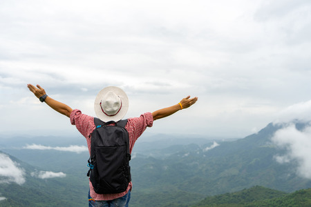 Backpack man standing raising arms relaxing fresh air enjoy serene mountains on vacation, Rear view.