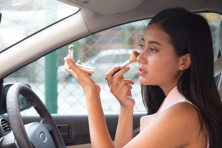Beautiful young woman sit in car on driver's seat looking at rear view mirror checking, brushing make up. Asian Girl applying blusher Cosmetic Powder Brush. woman applying dry cosmetic tonal foundation on face. 版權商用圖片