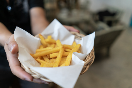 Cropped shot of man hand holding bowl of french fries fast food in bucket with copy space, close up.