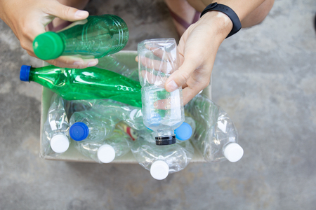 Hand holding clear and green recyclable plastic bottle putting in paper garbage bin for recycling.waste management and plastic reuse toenvironmental protection world concept. Reklamní fotografie