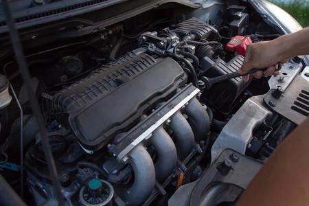 Meccanico, uomo tecnico che tiene la chiave che controlla il motore dell'auto. servizio auto, riparazione, riparazione, controllo manutenzione lavorando presso l'officina di riparazione auto. concetto di veicolo di ispezione.