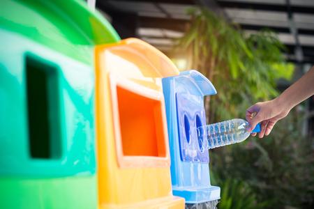 Abfallwirtschaft, Frau wirft Plastikflasche in den Papierkorb. Mülltrennung vor dem Abfallen in den Mülleimer, um die Welt zu retten, Umweltschutz. Umweltverschmutzung Müllrecycling-Management-Konzept.