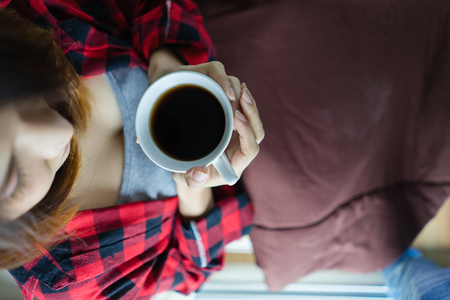 Woman hands holding hot coffee cup in bed, top view Asian girl with cup of coffee or tea in bed at home early in the morning.