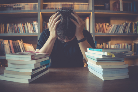 Stress and tired man under mental pressure while reading book preparing examination in library. Businessman stressed overworked studying piles of books on desk in public library.Headache, migraine, education, hard work, tired, overworking concept. Zdjęcie Seryjne - 122399361