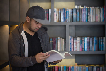 Young man reading book in library. Student in college study from book, knowledge in university concept. Study hard for exam. people, knowledge, education and school concept.