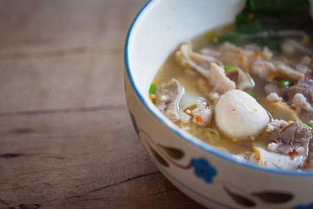 Thai noodle soup,Tom Yum in bowl on wooden background with copy space. Thai style food noodle in hot soup with pork and meatball.