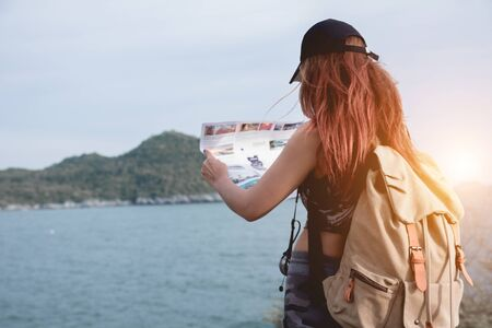 Hipster tourist hold and look map on trip, lifestyle concept adventure, traveler with backpack on mountain and blue sea landscape.Woman traveler with backpack checks map to find directions. Travel explorer Concept.