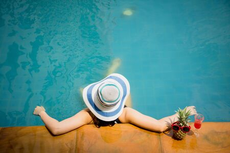 Woman in swimming pool with summer hat, top view. Happy Asian girl at edge pool side relaxing on vacation. Elegant travel refresh enjoying summer concept.