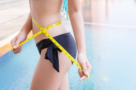Woman in sexy bikini with slim body measuring thigh with measurement type after diet with swimming pool in background. Young sport girl measuring thin waist body by measure tape checking waist size, close up. Diet, sport and heath concept Zdjęcie Seryjne