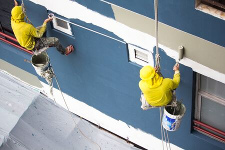painters hanging on roll, painting color on building wall. Young painting facade builder worker with roller brush, working on high building, working together concept. safety construction with lift ropt belt in city.