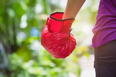 Woman wearing red boxer grove standing against green nature bokeh outdoor back view with copy space. business fighting victory concept. Stock Photo