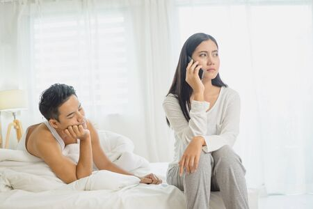 Depressed young woman sitting on bed calling on phone having problems with boyfriend.