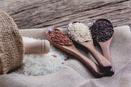 Thai jasmine and various rice in wooden spoon on wooden table . Jasmine rice, Mixed organic on sack texture background. top view with copy space. organic rice and healthy food concept.