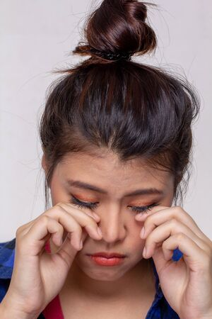 Young asian woman feeling hurt, itchy or irritate on her eyes afrer put contact lens into eyes. Girl crying tears on face, hands touching eyes isolated on white background.