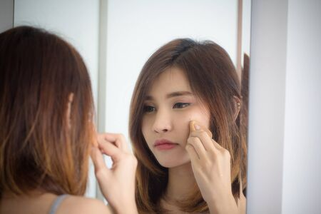Portrait beautiful asian girl applying powder puff foundationat mirror in bedroom. Young woman makeup of cosmetic looking in mirror. Cleaning face  beauty, health and wellness concept.