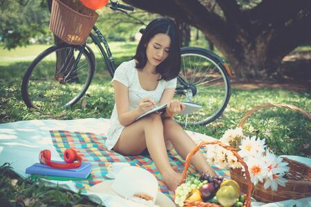 Young woman picnic in park with fruit basket writing note book under tree. Asian girl with flower, book ,coffee cup and headphones. Happy female in garden with bicycle in background. lifestyle in green nature outdoor.