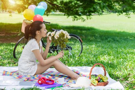 Young woman picnic in park with fruit basket. Asian girl with flower, book ,coffee cup and headphones. Happy female in garden with bicycle in background. lifestyle in green nature outdoor.
