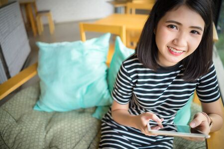 Young woman relaxing using tablet smile looking at camera.Happy Asian girl sitting on sofa holding tablet computer in hand. People lifestyle with technology concept.