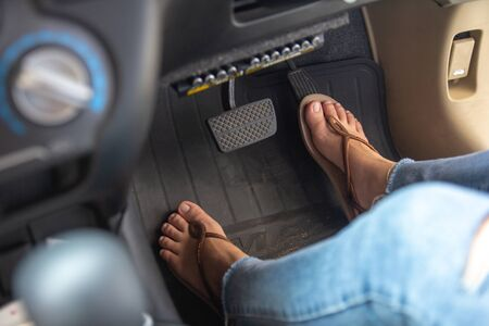 Woman foot driving car with shoe pushing on car speed pedal. Female feet with brake and accelerator pedals, car speed control concept.
