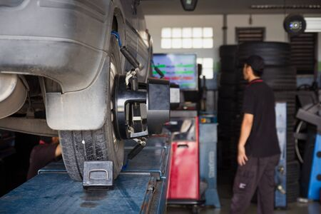 Car tyre alignment wheel balance at garage service workshop. Mechanic fixing car using wheel alignment device. computer wheel alignment. Balancing tire wheel machine. Stok Fotoğraf