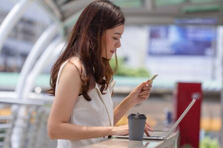Business woman hand holding credit card using laptop shopping online.Young happy Asian girl typing on notebook computer paying online by credit cards.Online payment, internet banking, people and technology concept.