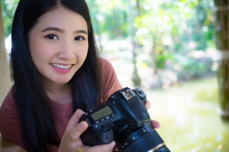 Woman photographer holding dslr camera in hands,  looking at camera.Young happy asian girl professional photographer with dslr camera at summer green park outdoor. Stok Fotoğraf