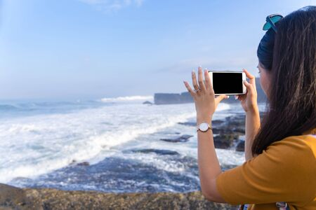 Young woman taking photograph with smart phone camera on the island beach, Back view.