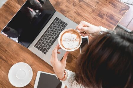 Young woman drinking coffee with laptop, cellphone and tablet on table in cafe.