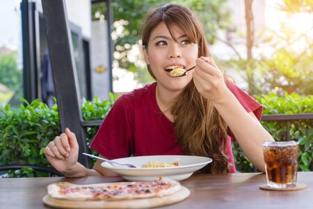 Young woman eating pasta, Spaghetti and pizza with soft drink on table in restaurant outdoor. Happy eating traditional Italian food, lifestyle concept. Hungry Asian girl having food alone. Stock Photo
