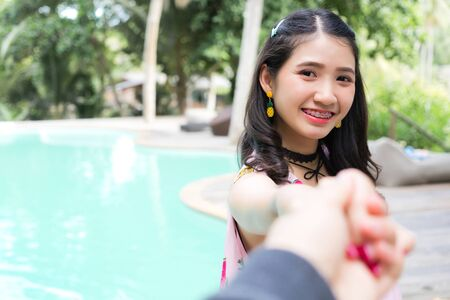 Young happy woman holding man hand leading to the beach. Couple in love on holiday by swimming pool. lovers enjoying summer vacation.Follow me, Tourist couple traveling together following to sea beach. Stok Fotoğraf