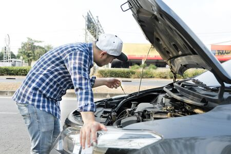 Man checking enginr lube oil level under car hood, fix broken car on the street.Mechanic inspection service and maintenance automotive repair car concept.