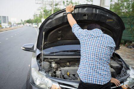 mécanicien portant des gants ouvre le capot de la voiture en vérifiant l'huile du moteur de la voiture sur la route après un problème de panne de voiture. Entretien du jeune homme, réparation des problèmes de réparation d'accidents de voiture à l'atelier de garage.