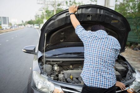 mechanic wearing gloves open car hood checking car engine oil on the road after car breakdown problem.Young man maintenance, fixing trouble car accident repair at garage workshop.