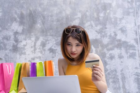 Young woman using laptop computer shopping online with credit card.Asian girl using credit card for internet shopping online technology with shopping bag in background.