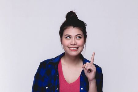 Young woman pointing finger up over white background.Happy Asian girl with funny face close up point finger up.