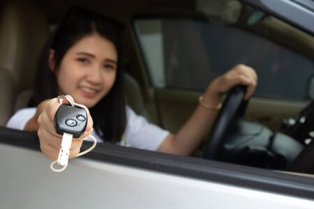 Asian car driver woman smiling showing car key.