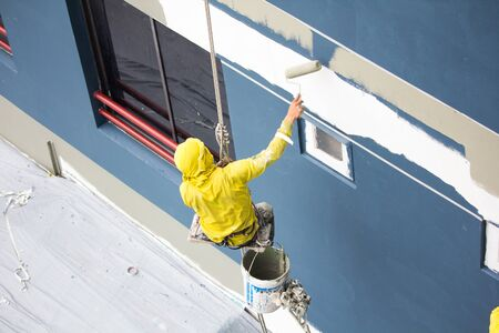 painters hanging on roll, painting color on building wall.facade builder worker with roller brush, working on high building.safety construction with lift rope belt in city.