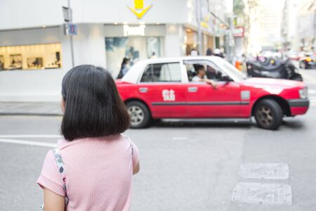 Young woman walking in Hongkong street with taxi cab in background. Traveler Asian girl in Hongkong city. Travel lifestyle concept.