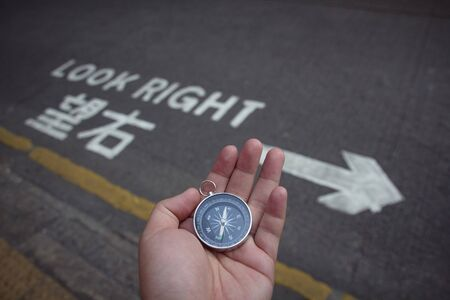 Hand holding compass in city over road sign. Travel tourist lost in city street using compass for right direction. adventure journey explorer finding destination lifestyle concept. Stock Photo
