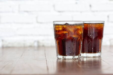 Two glass cool ice cola carbonated soft drink liquid fresh food with soda water on wooden table in restaurant, Close up.Sweet drinks beverage with ice cubes and bubble on white background. Stockfoto