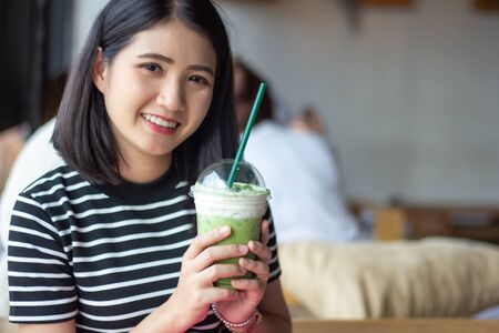 Smiling woman holding matcha green tea latte at coffee shop. Asian girl holding green tea glass in cafe morning. Focus on green tea glass.
