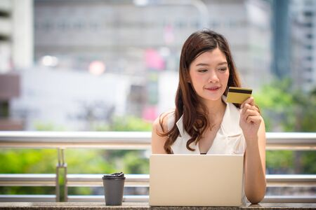 Business woman hand holding credit card using laptop shopping online.