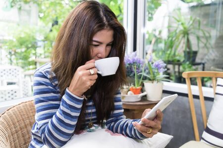 Young asian Woman drinking coffee and using mobile smartphone in the morning. Technology lifestyle concept. Focus on coffee cup. Stock Photo