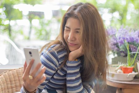 Happy young asian woman taking selfie or using mobile smart phone video call. Smiling young girl making selfie photo on cellphone.